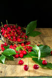 Cherries with green leaves in a basket on a wooden background Stock Photos
