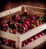 Cherries group in a wooden box. And dark background Royalty Free Stock Images