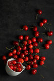 Cherries. Heap of sweet cherries in a Cup and scattered on a black background Royalty Free Stock Photo