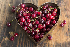 Cherries in Heart Cake Pan. On a Rustic Wooden Background stock photography