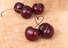 Cherries and heart on a wooden board Stock Photography