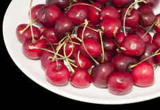 Cherries. Image of a white plate full of cherries on black background Royalty Free Stock Photos