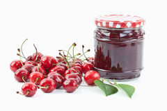 Cherries beside jar of cherry jam on white background,close up Royalty Free Stock Photography