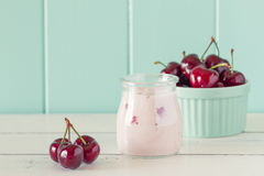 Cherries. A jar with cherry yogurt and some cherries in a turquoise classic whiteware baking bowl on a white wooden table with a robin egg blue background Royalty Free Stock Image