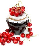 Cherries and jar of jam isolated on white. Royalty Free Stock Photography