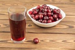 Cherries juice in glass and fresh cherries in bowl on wooden background. Cherries juice in glass and fresh cherries in bowl on old wooden background stock photo