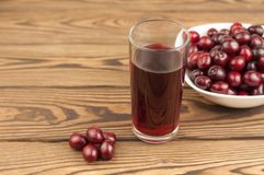Cherries juice in glass and fresh cherries in bowl on wooden background. Cherries juice in glass and fresh cherries in bowl on old wooden background royalty free stock photo