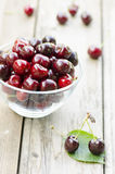 Cherries on leaf and in bowl. On wood background Stock Photo