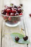 2 cherries on leaf and more cherries in bowl. On wood background Stock Image