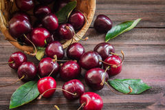 Cherries with leaves enough sleep from a basket. On a wooden background stock photography