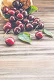 Cherries with leaves enough sleep from a basket. On a wooden background royalty free stock image