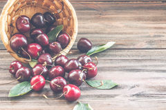 Cherries with leaves enough sleep from a basket. On a wooden background royalty free stock photo