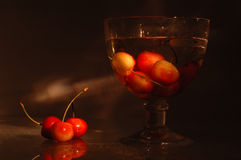 Cherries - light and shadows. Horizontal composition of cherries in water and on a glass cowered with water drops. Light painting technique Stock Photos