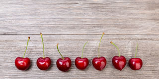 Cherries in line on wood. Some red cherries in a line  against wooden background Royalty Free Stock Images