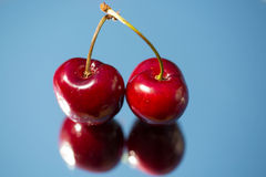 Cherries on a mirrow Stock Images
