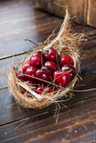 Cherries in nest on wooden background Royalty Free Stock Images