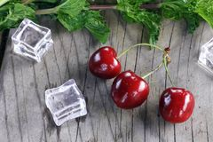 Cherries next to greens and ice cubes on a vintage wooden table royalty free stock image