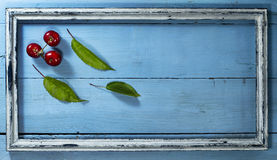 Cherries in old frame on a blue wooden background. Cherries with leaves in old frame on a blue wooden background stock image