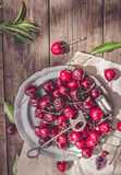 Cherries and old stone remover above Royalty Free Stock Photo