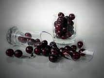 Cherries with overturned glass Royalty Free Stock Photo