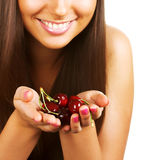 Cherries in palms. Close-up studio portrait of a girl holding in palms a bunch of cherries Royalty Free Stock Image