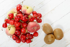 Cherries, and peaches in a glass cup with kiwis Royalty Free Stock Photo