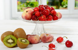 Cherries, and peaches in a glass cup with kiwis Royalty Free Stock Photos