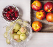Cherries, peaches, nectarines. On a white background, nectarines in a box, cherries in a white cup and peaches in a package royalty free stock image
