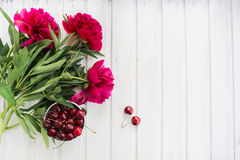 Cherries and peony Stock Photos