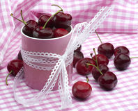 Cherries and Pink. Fresh Cherries In A Pink Jar On A Gingham Picnic Cloth Stock Photography