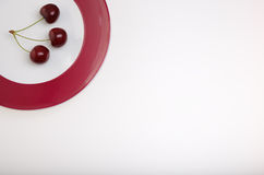 Cherries on a plate. Three cherries on a plate with a lot of white area Stock Image