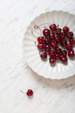 Cherries on a plate on a marble table Royalty Free Stock Photo