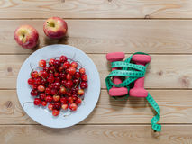 Cherries on plate red apples dumbbells  and measuring tape on w Stock Images