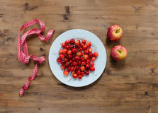 Cherries on plate red apples and measuring tape Royalty Free Stock Photos