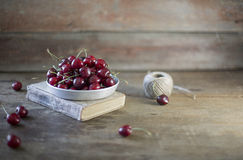 Cherries on a plate. On a wooden background royalty free stock photos