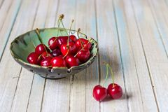 Cherries in a plate on a wooden table. Fresh red cherry Royalty Free Stock Images