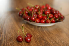Cherries. A plate of cherries on the wooden table, healthy snack stock photos