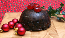 Cherries on the Pudding. A tasty Christmas Pudding with Cherries Holly and Baubles stock photo