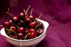 Cherries on red. Food still life of fresh organic cherries in bowl on red background Stock Photography