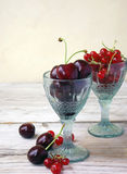 Cherries and red currants. In glass stock images