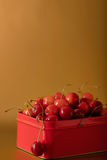 Cherries in a red metal box on a gold background. Royalty Free Stock Images