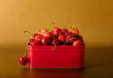 Cherries in a red metal box on a gold background. Stock Image