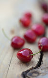 Cherries on a rough wooden surface Stock Images