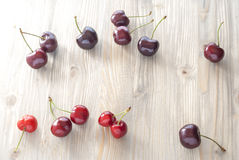 Cherries scattered on aged wood. Sun light Royalty Free Stock Photo