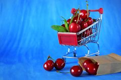 Cherries in a shopping trolley. Against blue background. Copy space Royalty Free Stock Photography