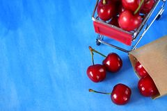 Cherries in a shopping trolley. Against blue background. Copy space Royalty Free Stock Image