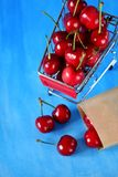 Cherries in a shopping trolley. Against blue background. Copy space Stock Images