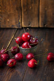 Cherries in silver cup on wooden background Stock Photos