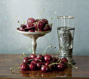 Cherries on a silver plate and an ancient glass Royalty Free Stock Image