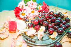 Cherries on a silver tray with rose petals stock photos